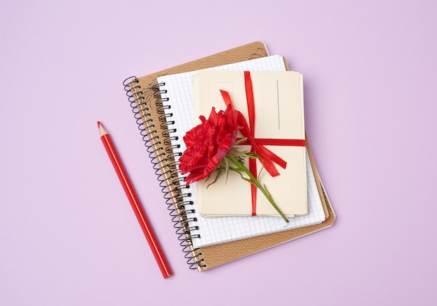 Rosa florescendo vermelha, uma pilha de cartões de papel vintage e cadernos sobre um fundo roxo