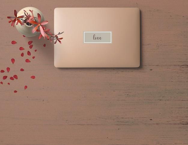 Rosa laptop na mesa de madeira-de-rosa com uma flor vermelha em um vaso e pétalas
