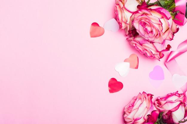 Rosa linda rosa, corações de confetes decorativos e fita rosa em rosa