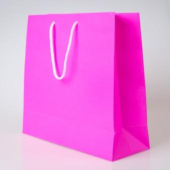 Rosa ou roxo sacola de compras um fundo branco e cópia espaço para texto simples ou produto