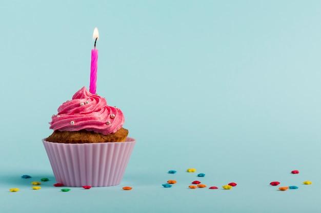 Rosa queimando velas em muffins decorativos com estrela colorida granulado contra o pano de fundo azul