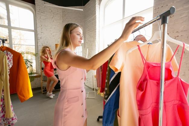 Rosa romântico. desgaste, loja de roupas durante as vendas, coleção de verão ou outono. mulheres jovens em busca de roupas novas. conceito de moda, estilo, ofertas, emoções, vendas, compras. novo shopping.