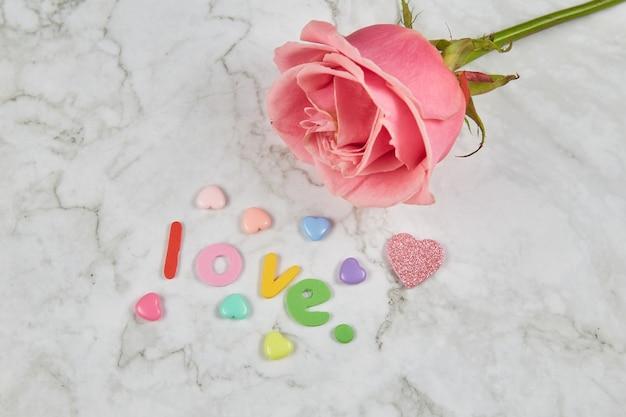 Rosa rosa com corações em tons pastéis e a palavra