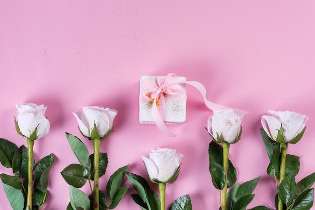 Rosa rosa e caixa de presente branca com fita rosa