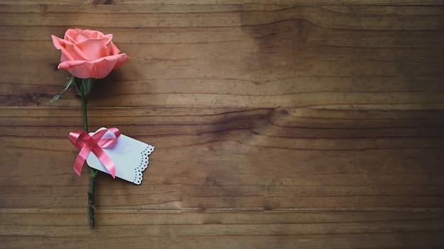 Rosa rosa e cartão de desejos amarrado com fita vermelha todos estes colocando na mesa de madeira.