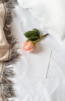 Rosa rosa em um travesseiro no quarto com uma nota ou cartão em branco. conceito de dia dos namorados.