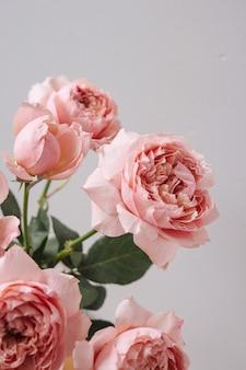 Rosa rosa em um vaso na mesa de madeira no fundo da parede cinza com vista lateral do espaço de cópia