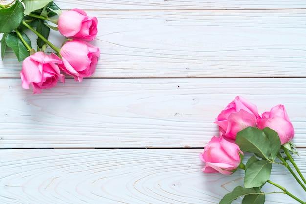 Rosa rosa em um vaso no fundo de madeira