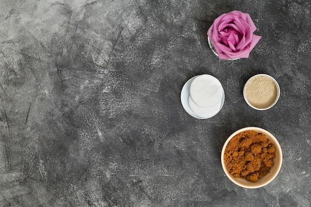 Rosa rosa flor; almofadas de algodão e tigelas de pó de café e argila rhassoul sobre fundo cinza concreto