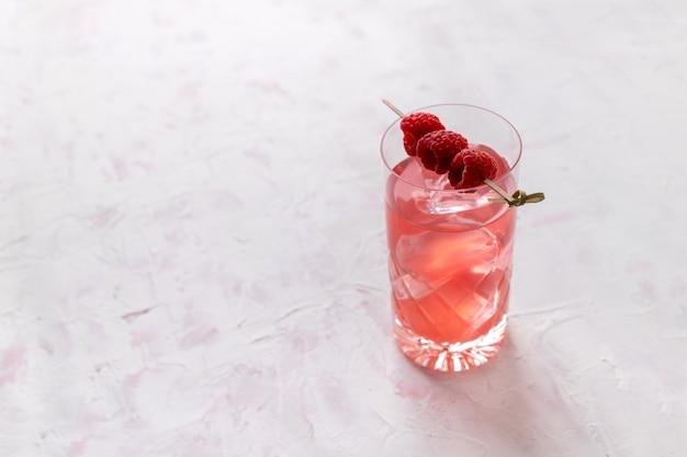 Rosa rosa gelado cocktail com framboesa em copo de cristal na mesa