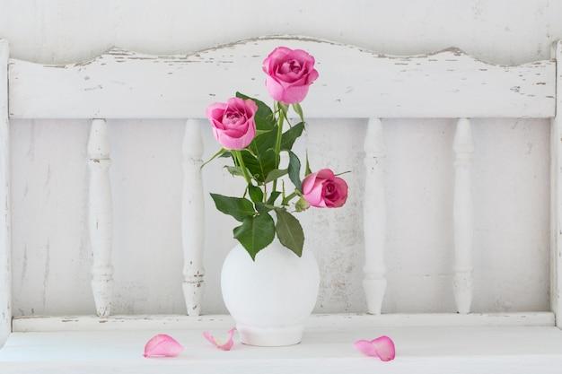 Rosa rosa na prateleira de madeira branca