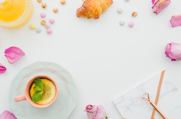 Rosa seca; croissant; doces; chá de limão; caneta e bloco de notas na mesa branca