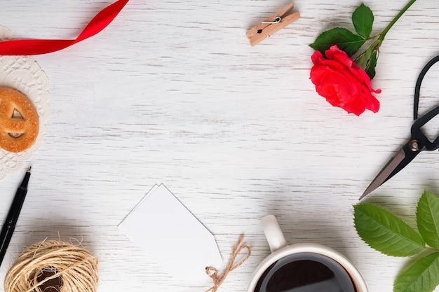 Rosa vermelha, café, tesoura e outros pequenos objetos na mesa de madeira branca, vista superior