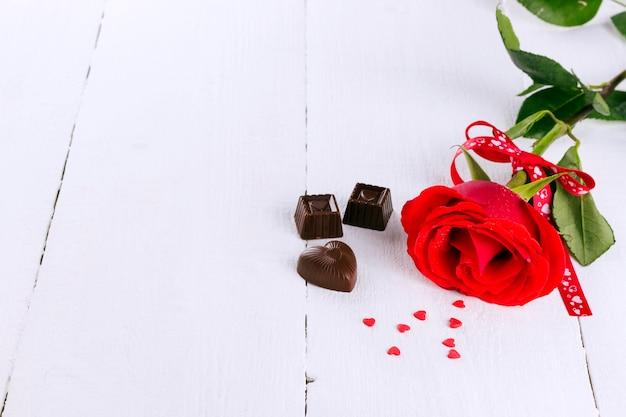 Rosa vermelha, chocolates em um fundo branco de madeira