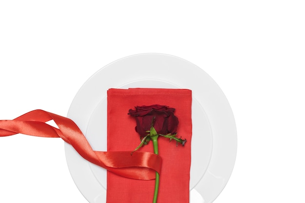 Rosa vermelha com fita no prato fundo branco. dia dos namorados.