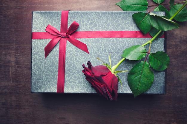Rosa vermelha e caixa de presente em uma mesa de madeira
