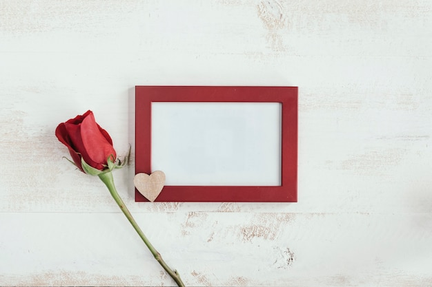 Rosa vermelha e coração de madeira com moldura