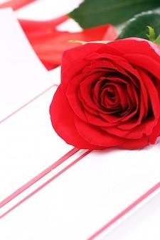 Rosa vermelha e envelope de férias