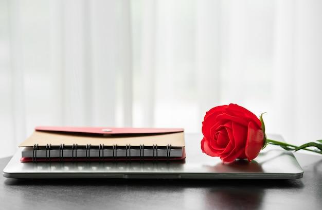 Rosa vermelha e o laptop no convés, conceito dos namorados
