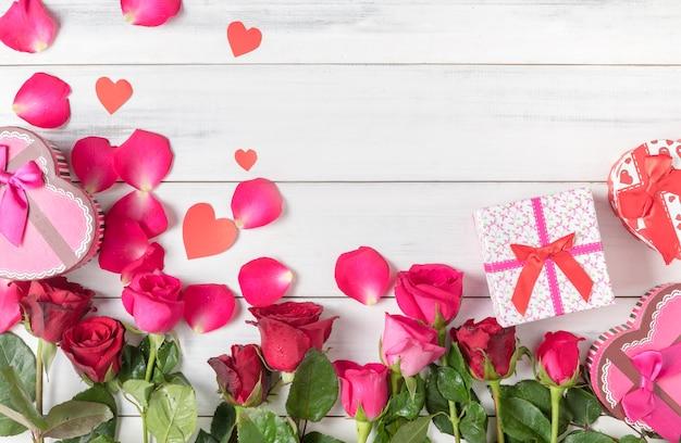 Rosa vermelha e rosa com caixa de presente no fundo branco de madeira, amor e conceito do dia dos namorados