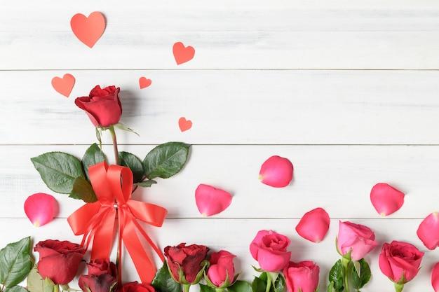 Rosa vermelha e rosa com coração de papel em fundo branco de madeira, conceito de dia dos namorados