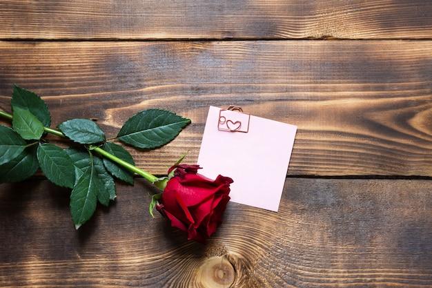 Rosa vermelha em fundo de madeira com copyspace e adesivo com um clipe de papel e um coração, um lembrete em uma folha de nota.