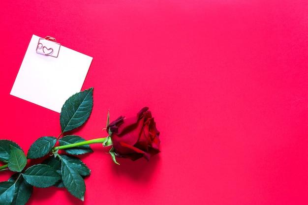 Rosa vermelha em fundo vermelho com copyspace e adesivo com um clipe de papel e um coração, um lembrete em uma folha de nota.