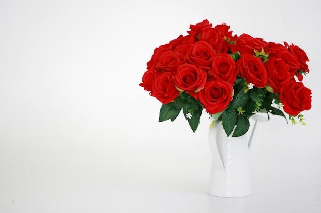 Rosa vermelha em um vaso branco sobre branco