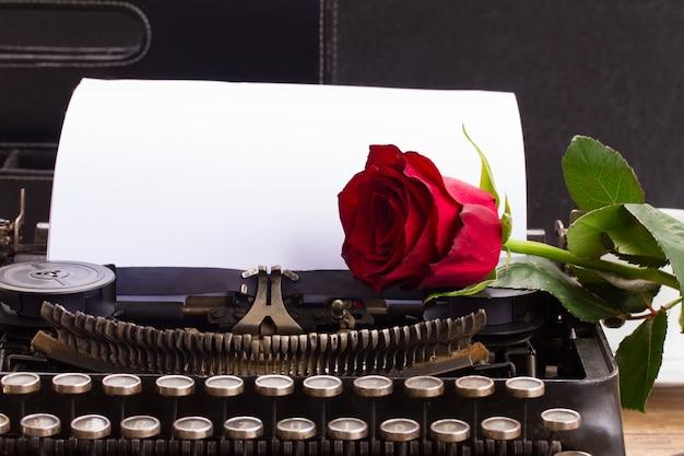 Rosa vermelha em uma máquina de escrever vintage com página em branco