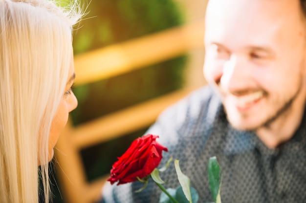 Rosa vermelha entre o rosto do casal