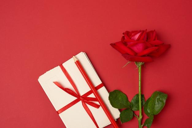 Rosa vermelha florescendo, uma pilha de cartões de papel vintage e lápis de madeira vermelho