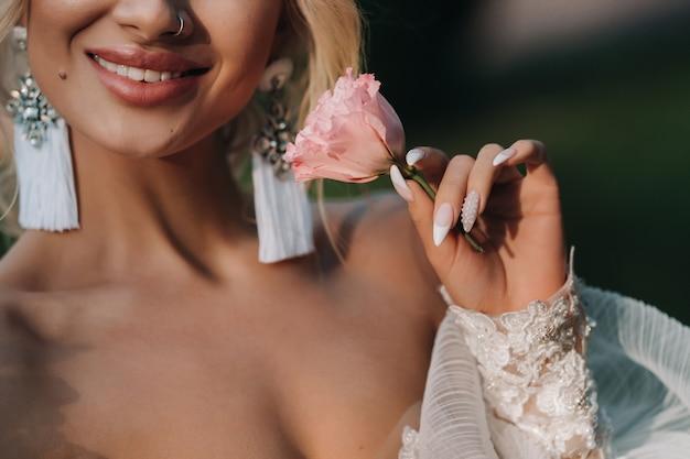 Rosa vermelha nas mãos da noiva.