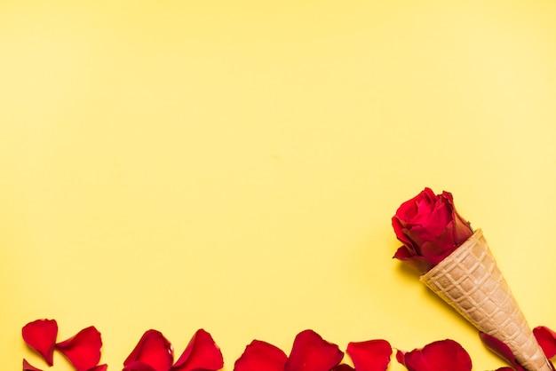 Rosa vermelha no cone waffle na mesa amarela