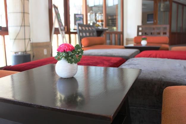 Rosa vermelha no pequeno vaso colocado na mesa com o assento