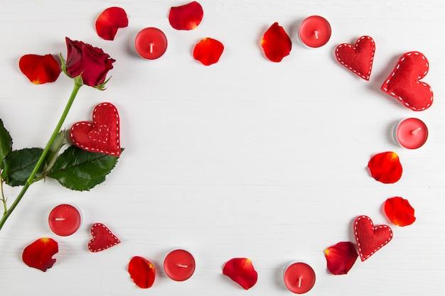 Rosa vermelha, pétalas, velas e corações na mesa branca.