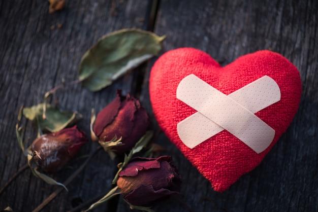 Rosa vermelha seca com papel vermelho em forma de coração partido em fundo de madeira