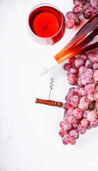 Rosa vinho e cacho de uva. bebida alcoólica em um copo de vidro