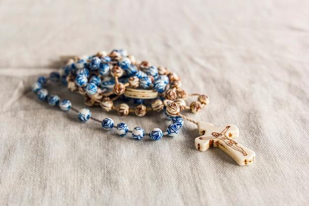 Rosário marrom com detalhes em azul com imagem de jesus na cruz em um pano bege