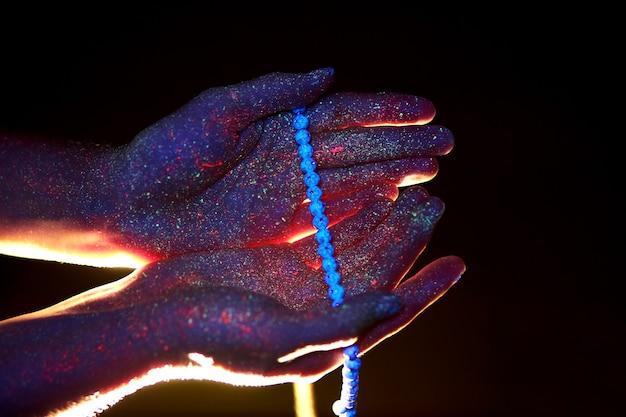 Rosário na mão, oração. ilumine pelas palmas das mãos em ultravioleta, deus e religião, contas. luz divina através de seus dedos, profeta muhammad