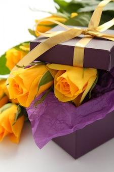 Rosas amarelas e caixa de presente roxa em um fundo branco