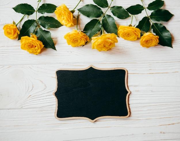 Rosas amarelas e um quadro de piture em uma mesa de mesa branca