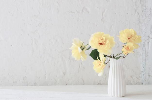 Rosas amarelas em um vaso branco na parede branca do fundo