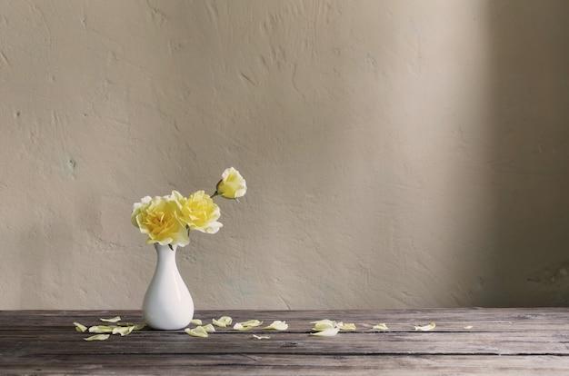 Rosas amarelas em um vaso branco na parede do fundo