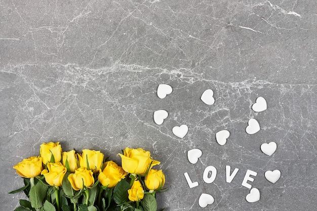 Rosas amarelas, palavra amor e corações brancos em cinza