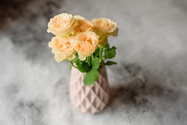 Rosas bege frescas bonitas em um vaso da argila em um fundo concreto. colocação e decoração de uma mesa