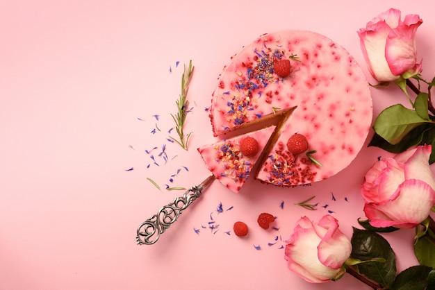 Rosas bonitas e delicioso bolo de framboesa com frutas frescas, alecrim, flores secas. vegetariana, conceito de comida vegan