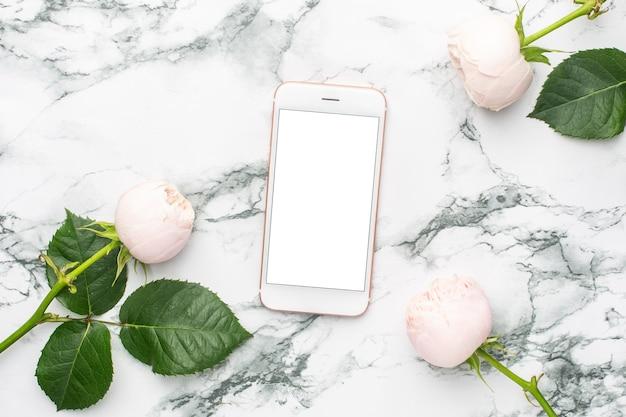 Rosas brancas com telefone celular em fundo de mármore branco e preto com copyspace