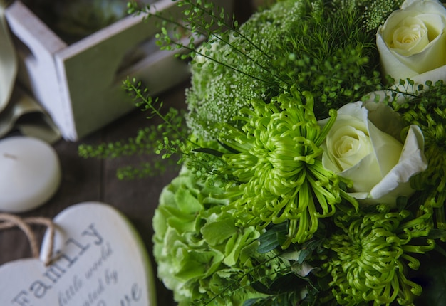 Rosas brancas e buquê de crisântemos verdes com símbolos de madeira ao redor.