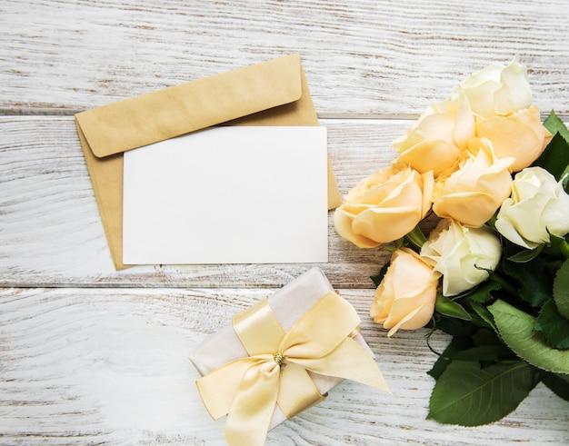 Rosas brancas e cartão em uma mesa de madeira velha