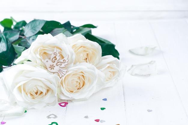 Rosas brancas e pombo-torcaz